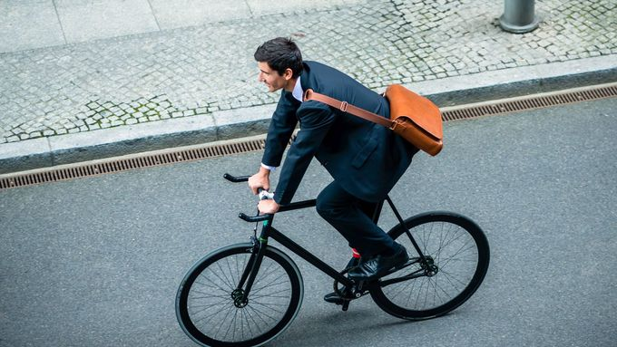 Young man wearing business suit while riding an utility bicycle